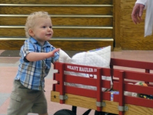 Jackson Blum (age 1) pushes his wagon that was purchased at the Community Thrift Shop. He is wearing re-treasured blue plaid button down shirt and tan shorts.