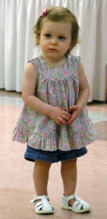 Lilah Blum (age 1) modeling a cute summer top, demim shorts and white leather sandles, all purchased at the Community Thrift Shop.