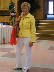 Community Thrift Shop manager, Sue Harris is modeling a bright yellow Talbots jacket, red and white striped boat neck top and white jeans. She is carrying a brightly striped canvas bag and red chiffon scarf. All garments and accessories were purchased at the Thrift Shop.